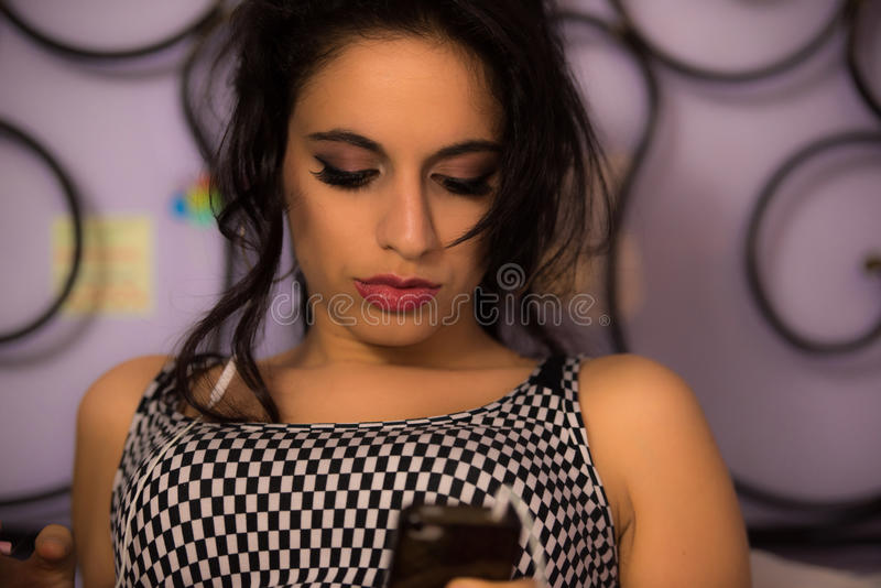 Beautiful girl with professional make-up smoking a sigarette and looking at her phone royalty free stock photo