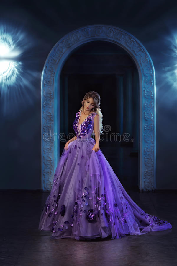 Beautiful girl in a purple dress. Beautiful, young, blond woman in a luxurious, purple, long dress. Queen walking in the palace. Fairy Photo. Creative toning stock image