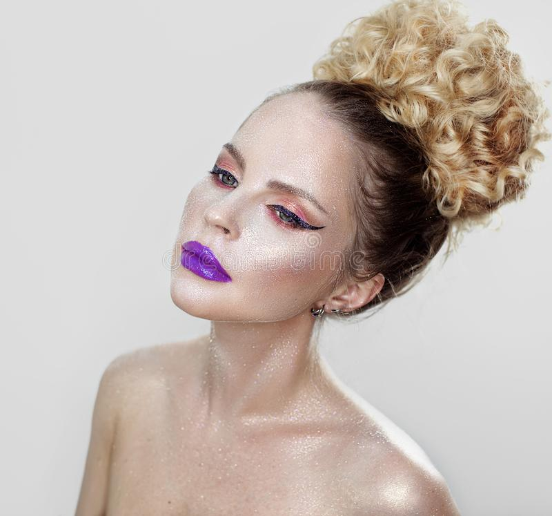 Beautiful girl with purple lips. Beautiful girl with curly hair in hairstyle with glitter and purple lips on white background royalty free stock image