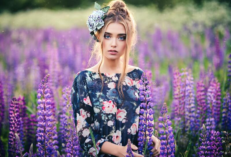 Beautiful girl in a purple lupin field with a flower on her head made of genuine leather and silk. Outdoor portrait. Beautiful young woman in a purple lupin royalty free stock photography
