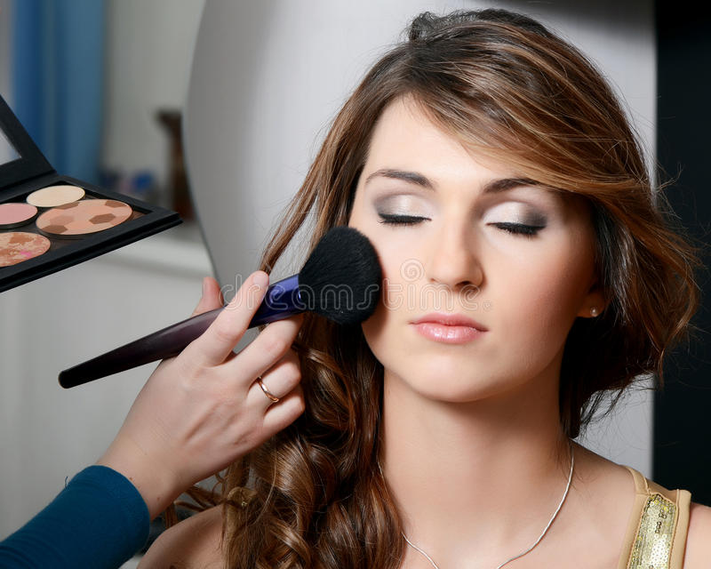 Girl put the makeup on the face stock photos