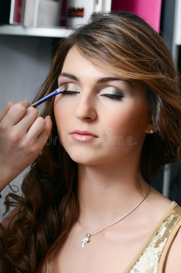 Girl put the makeup on the face stock photography