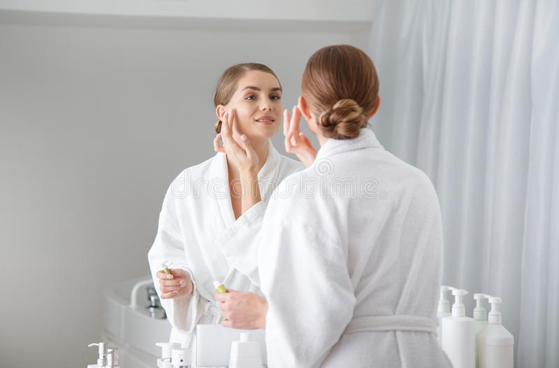 Beautiful girl putting cream on her face in bathroom. Joyful young woman is standing in front of the mirror and applying moisturizer on her cheek. She is smiling stock photography