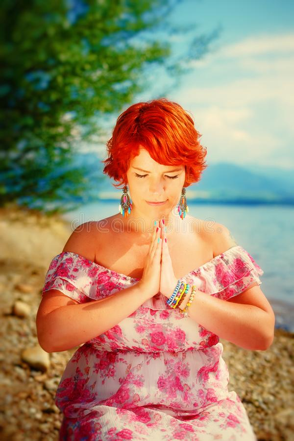 Beautiful girl with radiant red hair in sommer dress in a meditative spiritual gesture of prayer. royalty free stock image