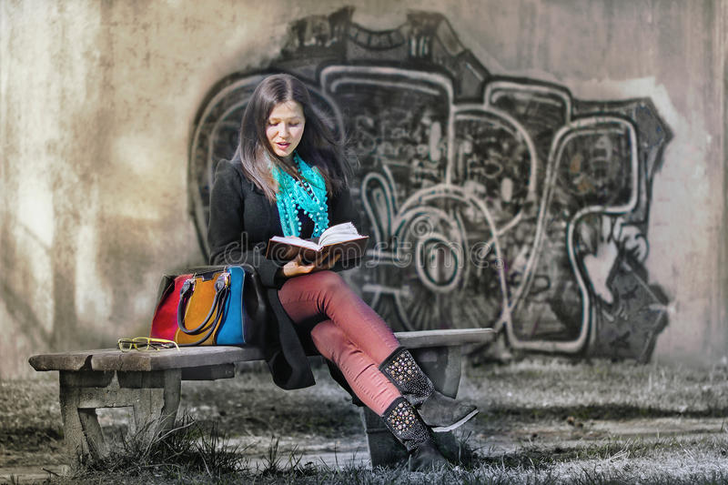 Beautiful girl reading a book in a park near a graffiti wall royalty free stock images