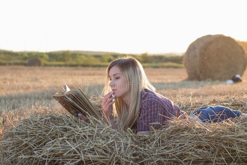 Beautiful girl reading a book at sunset in a haystack stock photo