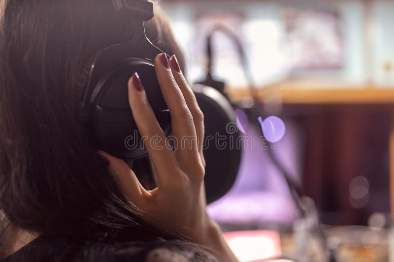 Beautiful girl records a song in a professional Studio royalty free stock photos