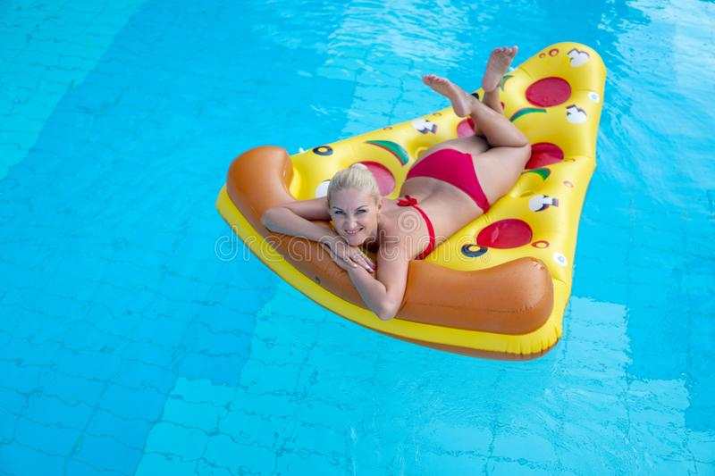 Beautiful girl in a red bathing suit floating on an inflatable mattress in the form of pizza in the swimming pool, tourist hotel royalty free stock photo