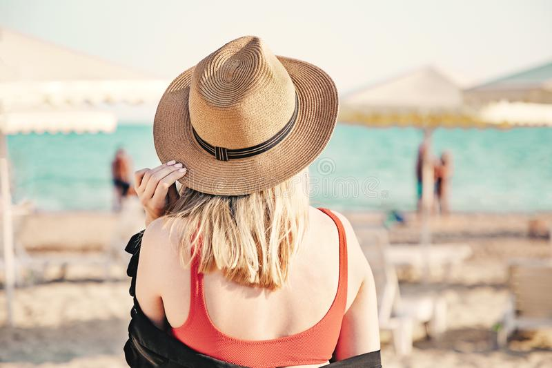 Beautiful girl in a red bikini and straw hat on the beach. Back view. White sand, blue water and beach umbrellas on the stock photography