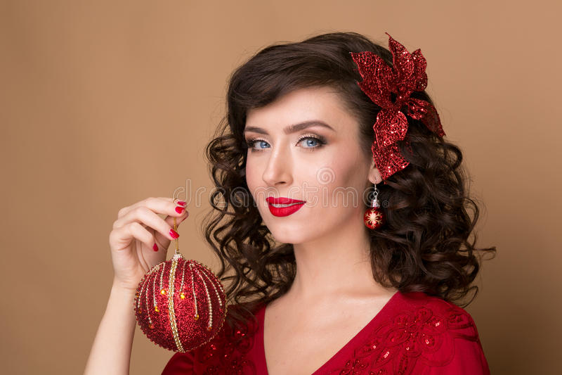 Beautiful girl with a red Christmas ball. In hands, studio close-up portraits, the New Year royalty free stock image