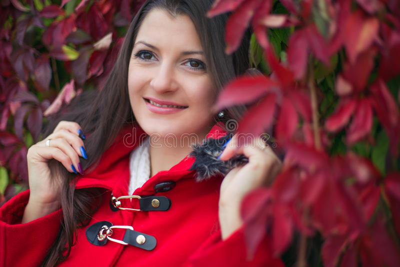 Beautiful girl in a red coat royalty free stock images