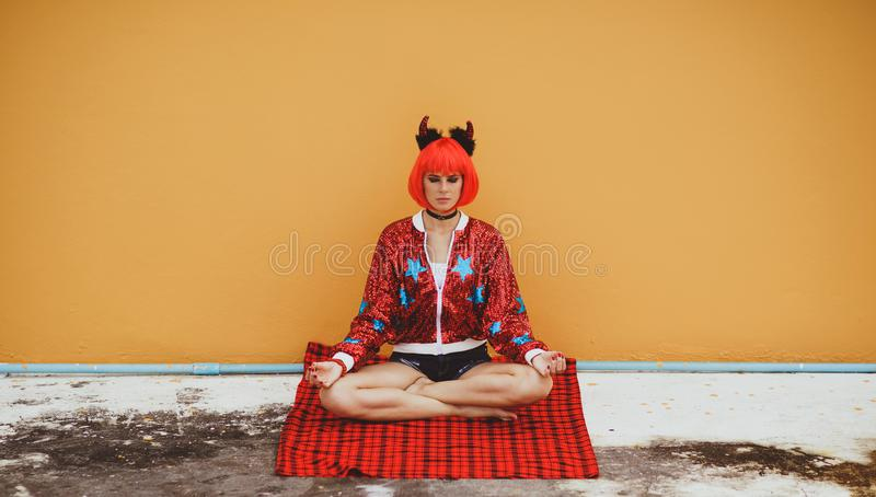 Beautiful girl in red devil costume sitting in yoga pose in anticipation of Halloween. Wears a red wig and horns. The royalty free stock photos