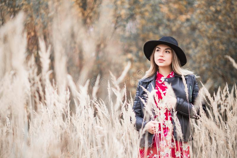 Beautiful girl in a red dress and black jacket walks among the tall grass in the field royalty free stock images