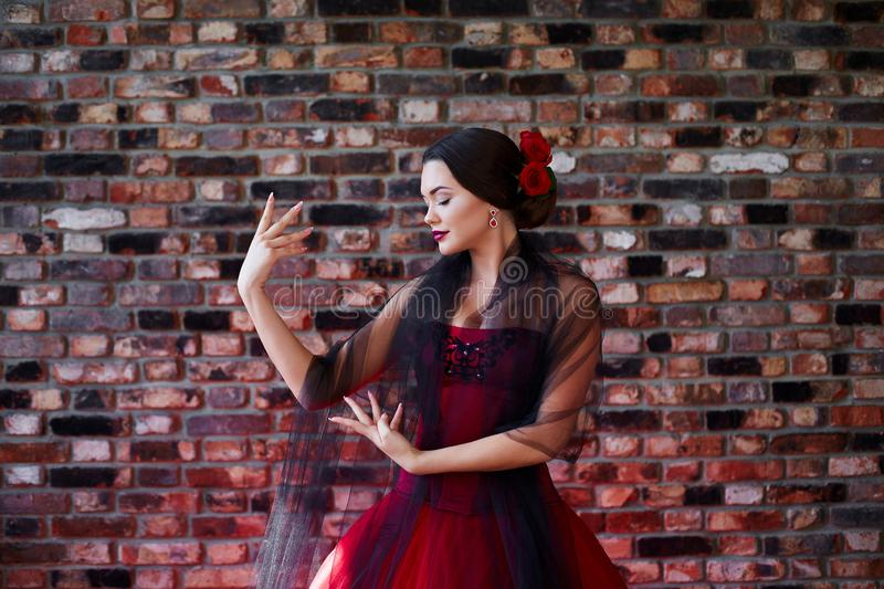 Beautiful girl in the red dress is dancing. Latin style. stock photos