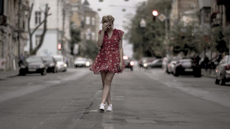 Beautiful girl in red dress posing for camera at urban road with cars royalty free stock photos