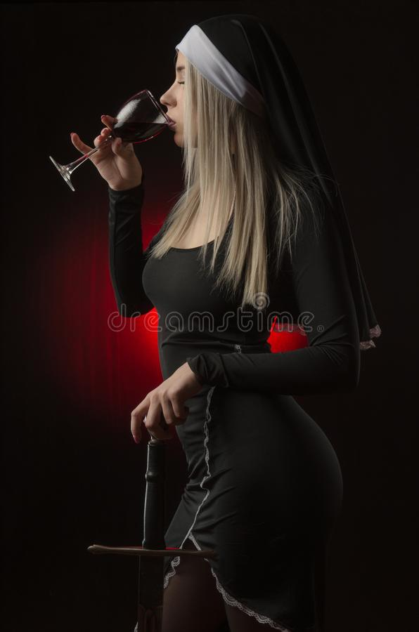 Beautiful girl in a red dress with a sword and a glass of wine. Posing on a black background in the Studio blonde royalty free stock photography