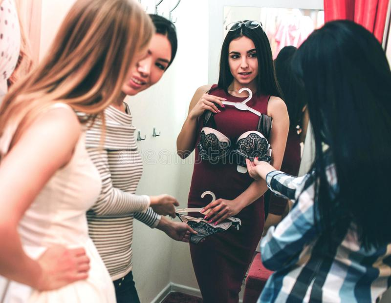 Beautiful girl in red dress is trying on herself bra. She is looking at her friends while they are looking at bra and royalty free stock images