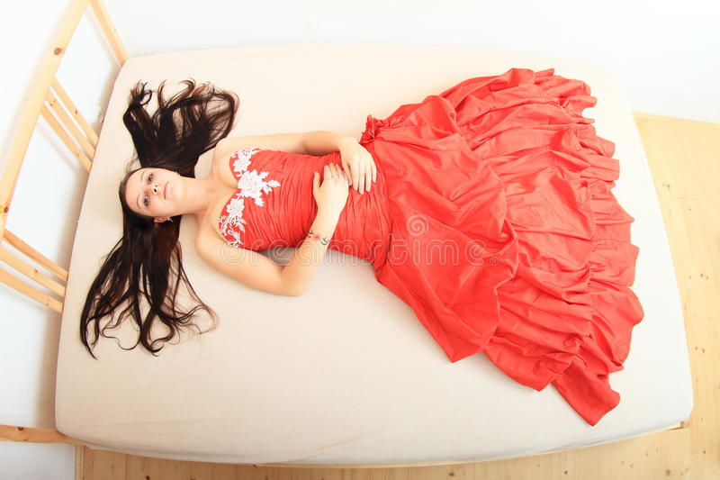 Beautiful girl in red evening dress on bed royalty free stock photos