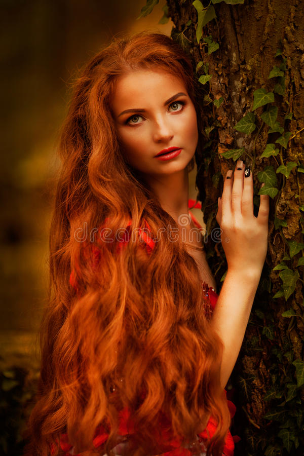 Beautiful girl with red hair in autumn park royalty free stock photography