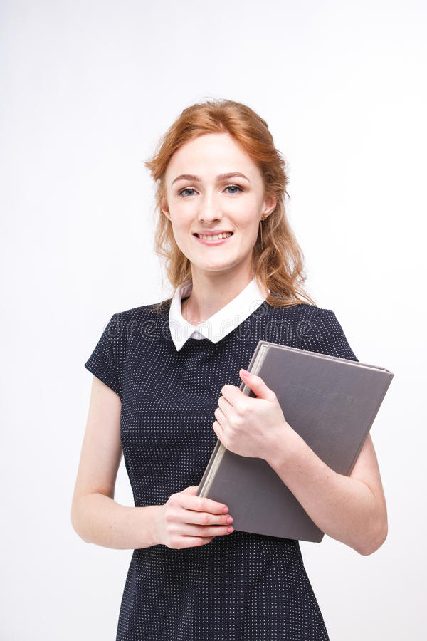 Beautiful girl with red hair and gray book in hands dressed in black dress white isolated background. Beautiful girl with red hair and gray book in hands dressed royalty free stock images