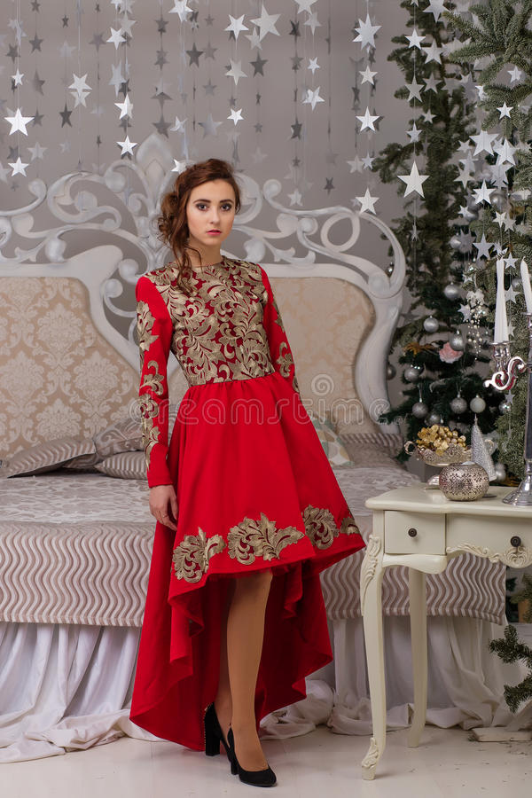 Beautiful girl in red long dress at the Christmas tree royalty free stock photography