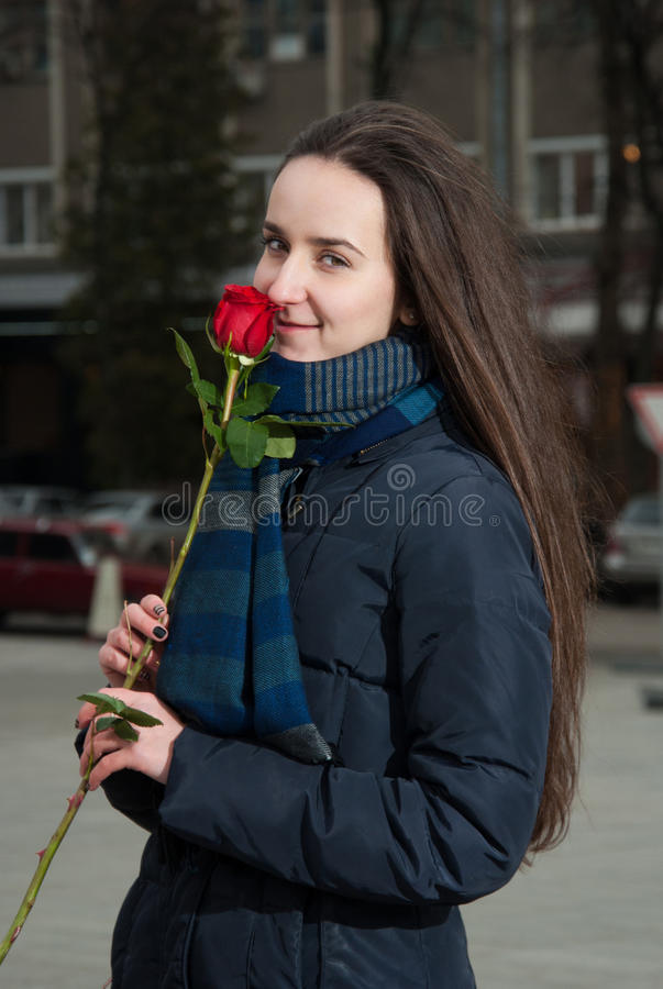 Beautiful girl with red rose in hand smiling stock photography