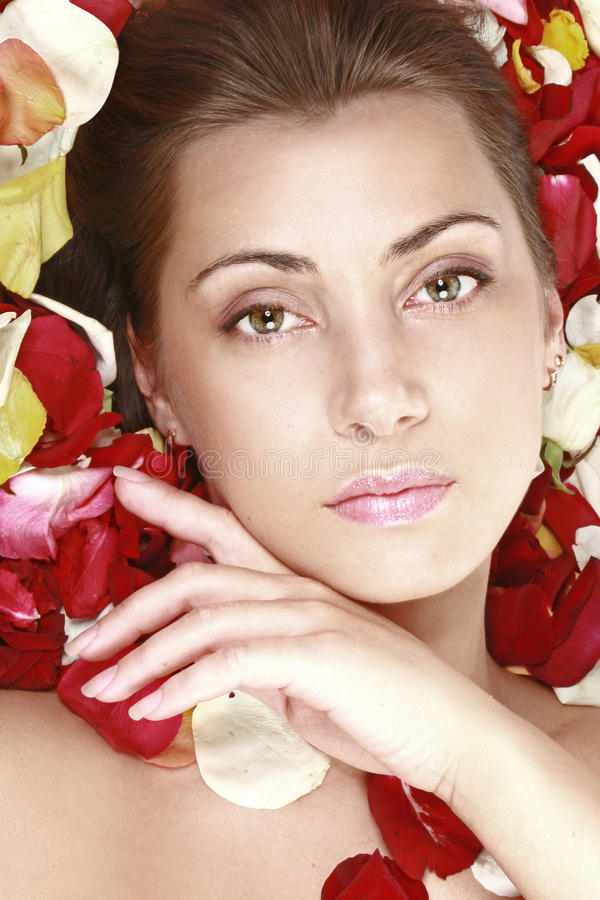 Beautiful girl with red roses petals stock images