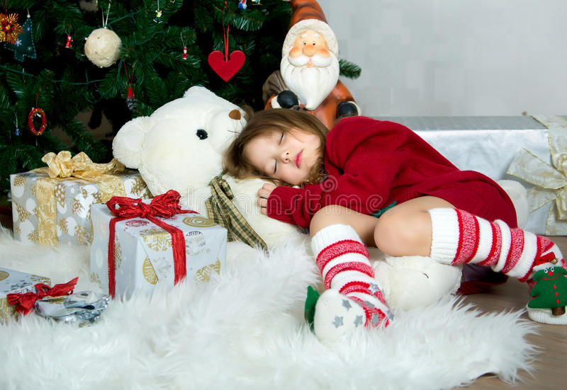 Beautiful girl in red sweater waiting Christmas and New year celebration lying under the X-mas tree royalty free stock photography