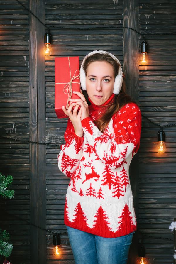 Beautiful girl in a red sweater wondering what inside christmas box royalty free stock photos