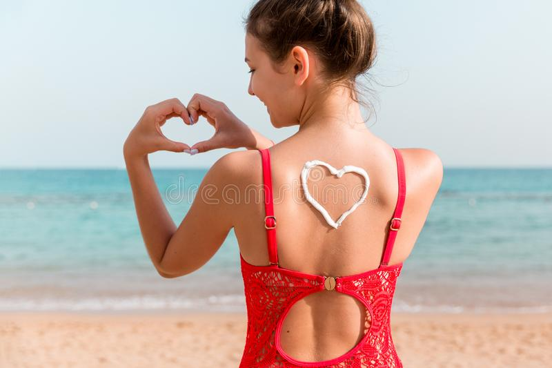 Beautiful girl in red swimsuit with sunscreen in shape of heart at the back at the beach.  stock image
