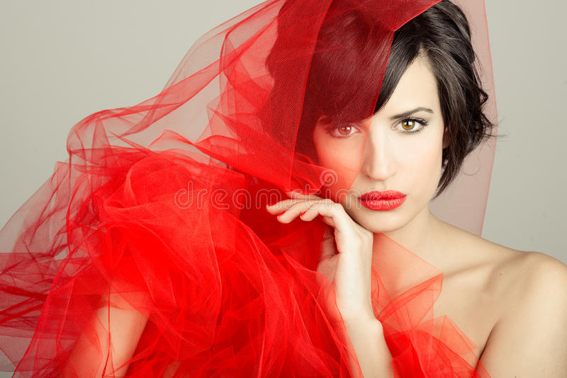 Beautiful girl with a red tulle. Studio photograph stock photo