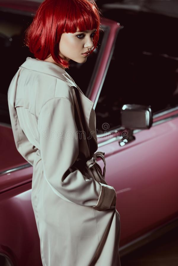 beautiful girl in red wig and stylish trench coat looking away royalty free stock photo