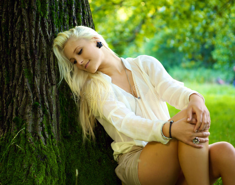 Beautiful girl relaxing. A young beautiful girl is relaxing against a tree on a sunny day royalty free stock photography