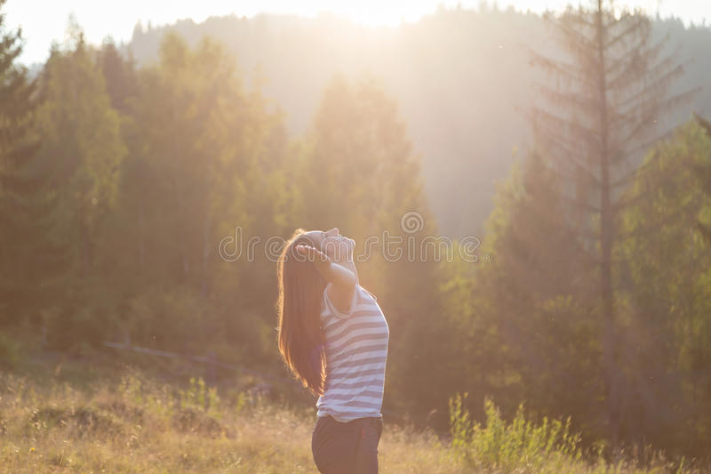 Beautiful girl, relaxing with her hands up. On the mountain, at sunset royalty free stock photography