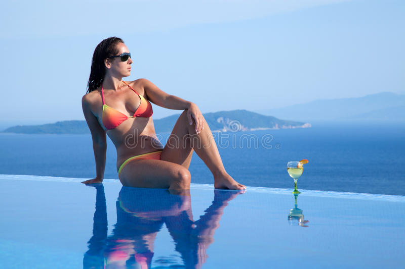 Beautiful girl is relaxing in an infinity pool. With a glas of wine royalty free stock photography