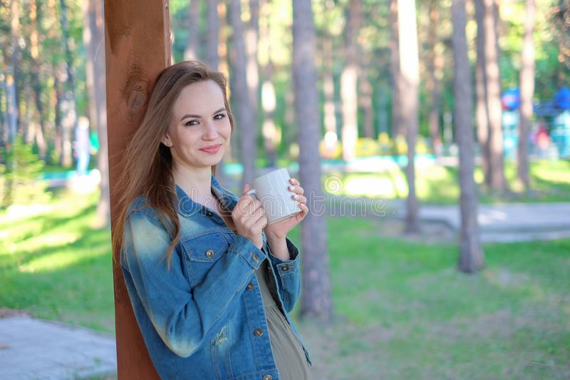 Beautiful girl relaxing in the park and drink coffee royalty free stock photo