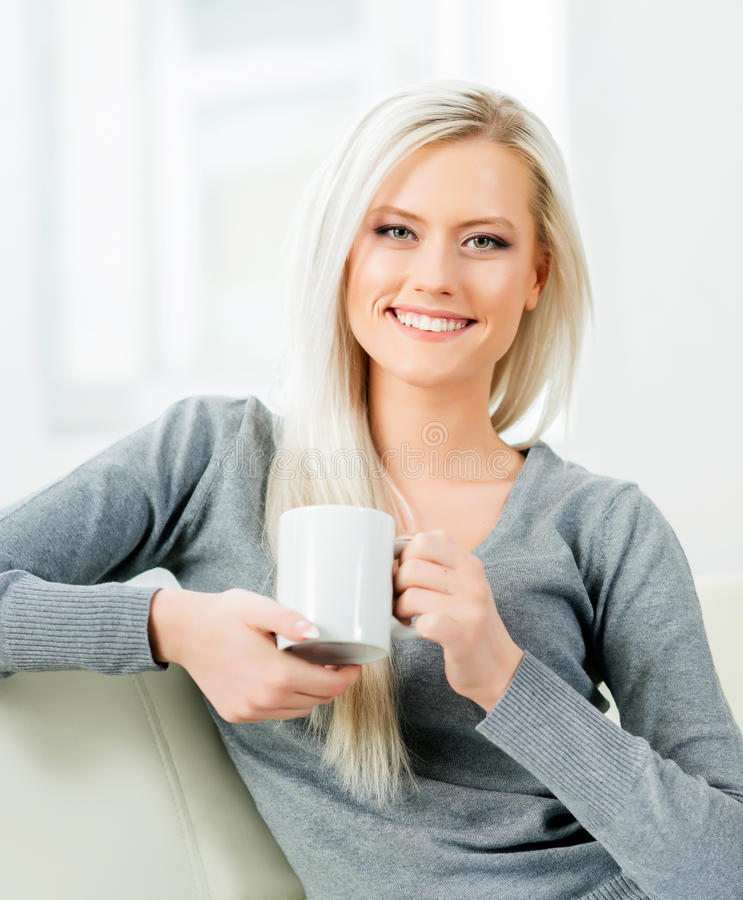 Beautiful girl relaxing on a white sofa at home and drinking tea.  royalty free stock photography