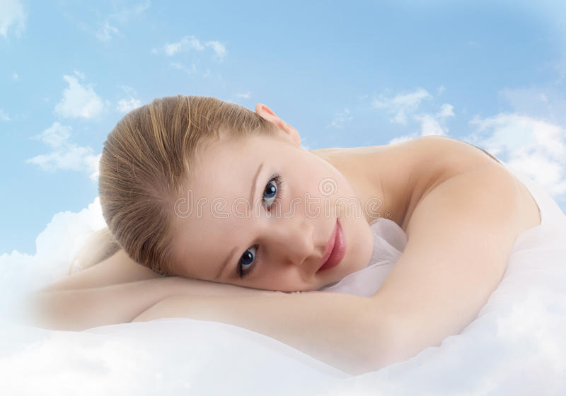 Beautiful girl is resting in the clouds. Young beautiful girl is resting in the clouds stock photography