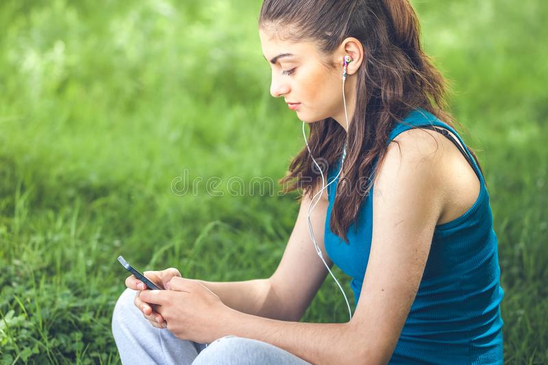 Beautiful girl resting in forest speak by cell phone, sports girl stock photography