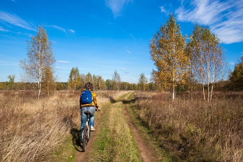 A beautiful girl rides a bicycle on a dirt road in the middle of a yellow autumn field and forest stock image