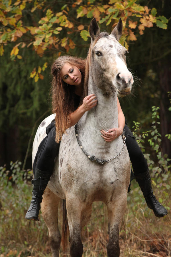 Beautiful girl riding a horse without bridle or saddle. In autumn stock image