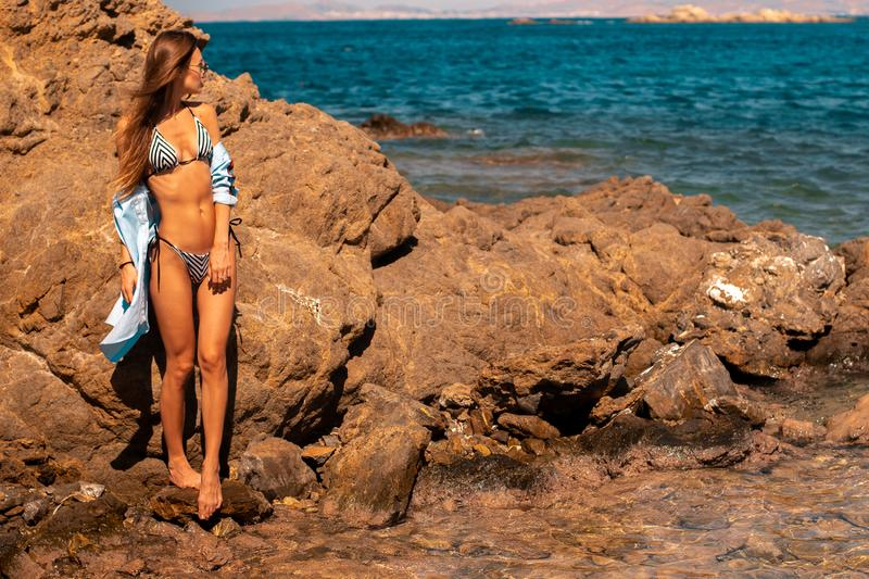 Beautiful lady on the rocks by the sea. Beautiful girl on the rocks by the sea stock photography