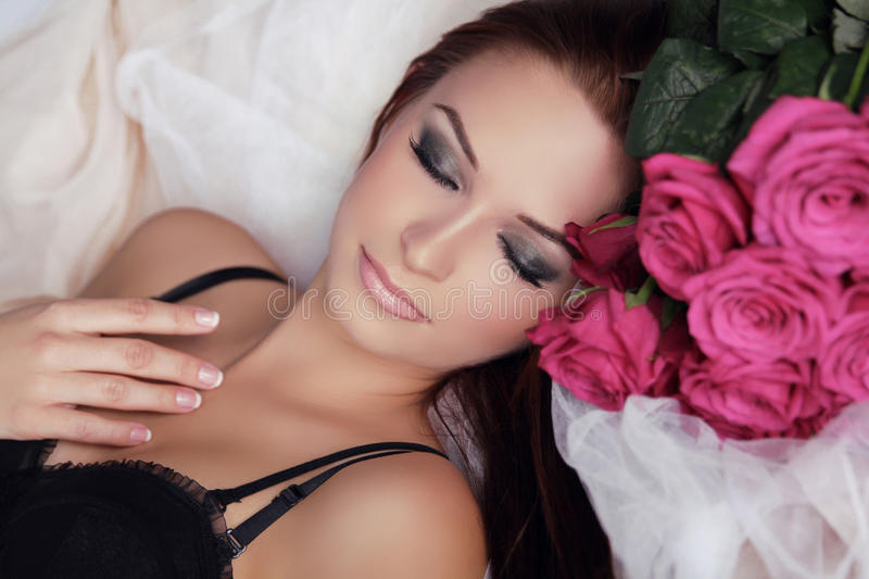 Beautiful Girl With Roses Flowers. Beauty Model Woman Face. Perfect Skin. Professional Make-up. Relax. stock images