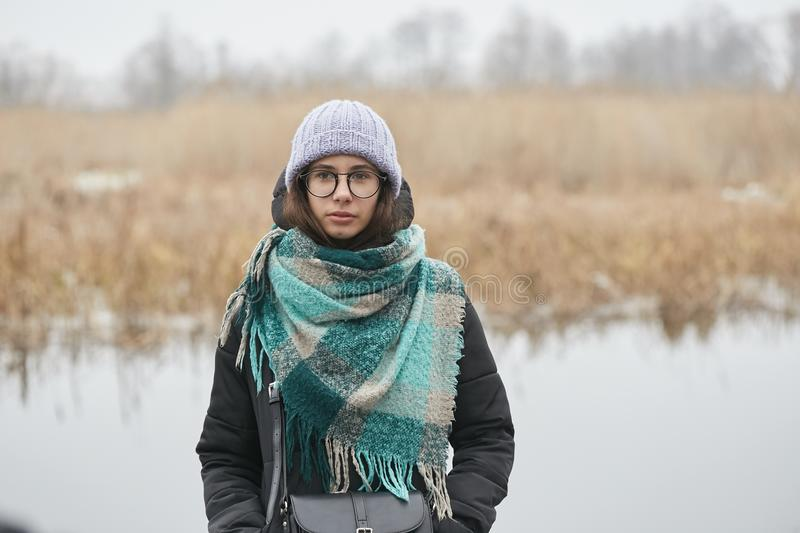 Beautiful girl in round glasses and a knitted hat. stock photography