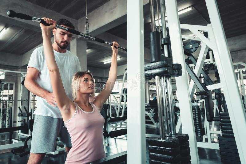 Beautiful Girl is Rowing Exercise With Bodybuilder Equipment in Fitness Club.,Portrait of Strong Woman doing Working Out Calories. Burning in Gym With Trainer stock image