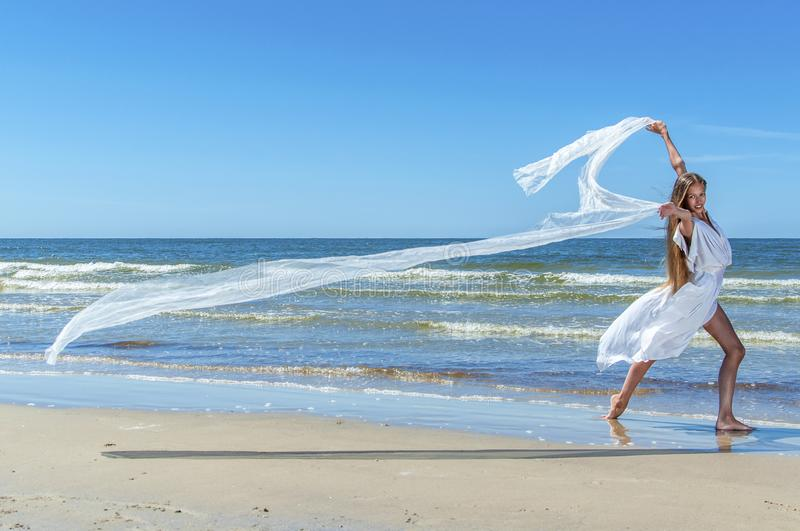 Beautiful girl running on the beach stock photos