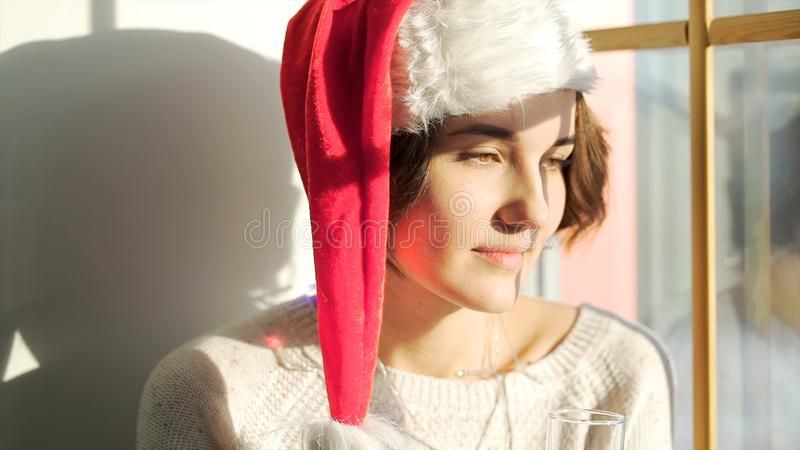 Beautiful girl in Santa Claus hat with a glass of champagne looking out of the window, Merry Christmass and New Year stock photo