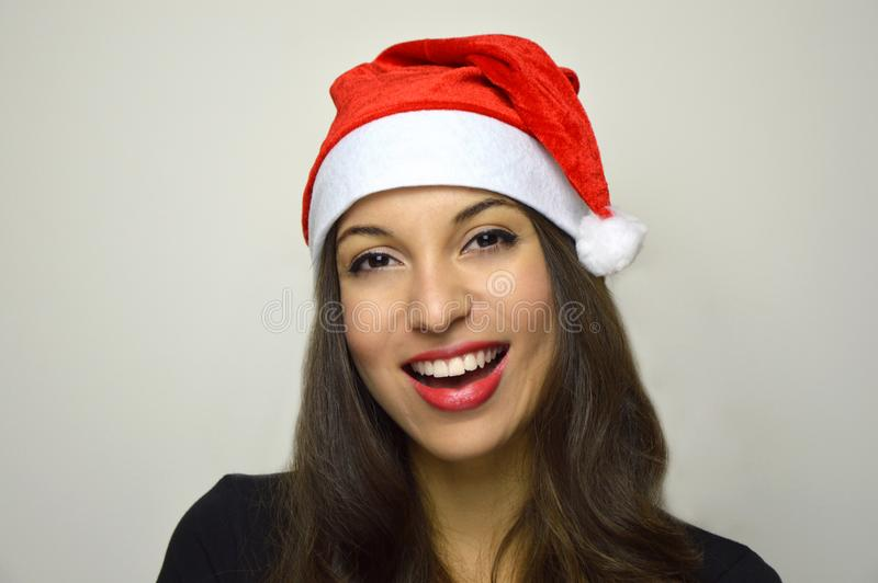 Beautiful girl with Santa Claus hat smiling at camera on white background royalty free stock photo