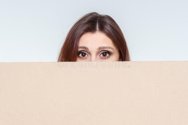 Beautiful girl scared looks out for cardboard blank banner for inscriptions. plate with space for text.  royalty free stock photos