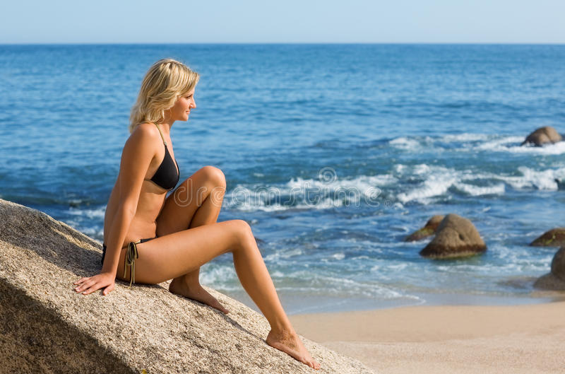 Beautiful girl by the sea. Beautiful girl is sitting on a rock by the sea royalty free stock image